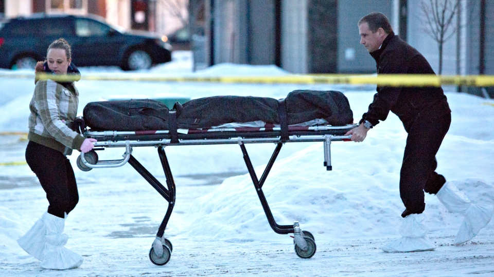 The body of a victim is carried out of a north Edmonton home where multiple deaths occurred in an overnight shooting in Edmonton on Tuesday, Dec. 30, 2014. (Jason Franson / THE CANADIAN PRESS)