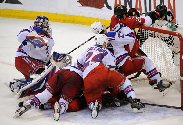Ottawa Senators' Chris Neil hangs from the cross-bar as his team scores while New York Rangers' Henrik Ludqvist looks at his teammates pile up in the crease during the third period of game six of first round NHL Stanley Cup playoff hockey action at the Scotiabank Place in Ottawa on Monday, April 23, 2012. THE CANADIAN PRESS/Sean Kilpatrick