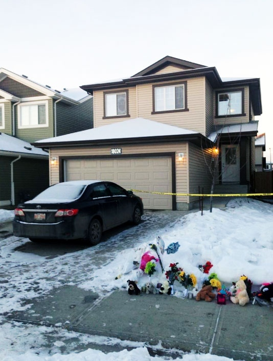 A memorial grows outside an Edmonton home where seven bodies were found Wednesday, Dec. 31, 2014. (Melanie Nagy / CTV News)