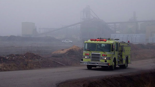 A fire truck drives through the fog at the Lakeland Sawmill in Prince George, B.C., Tuesday, April 24, 2012. (Andrew Johnson / THE CANADIAN PRESS)