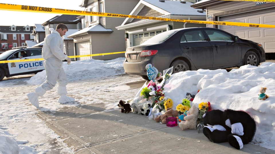 Flowers and stuffed animals lay on the sidewalk as police continue to investigate the scene where multiple shooting deaths occurred in a north Edmonton home, in Edmonton, Alta., on Wednesday, Dec. 31, 2014. (Jason Franson / THE CANADIAN PRESS)