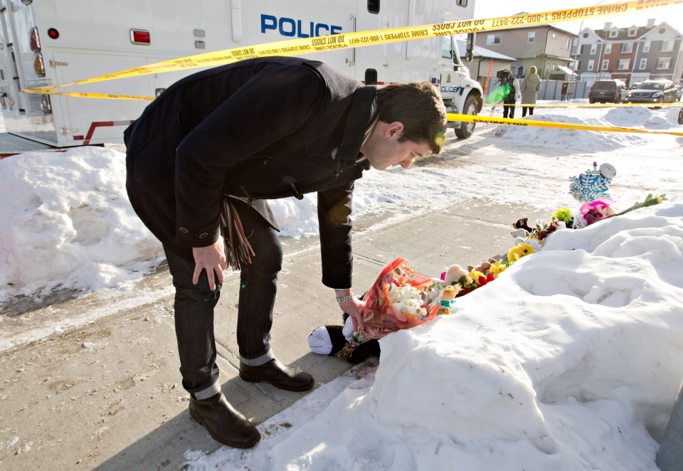 Edmonton Mayor Don Iveson lays flowers at the scene where multiple shooting deaths occurred in a north Edmonton home, as police continue to investigate, in Edmonton, Alta., on Wednesday, Dec. 31, 2014. (Jason Franson / THE CANADIAN PRESS)
