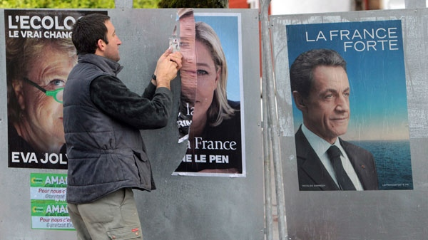 An employee removes election posters for Marine Le Pen after the first round of presidential elections, in La Bastide Clairence, southwestern France, Tuesday, April 24, 2012. (AP / Bob Edme)