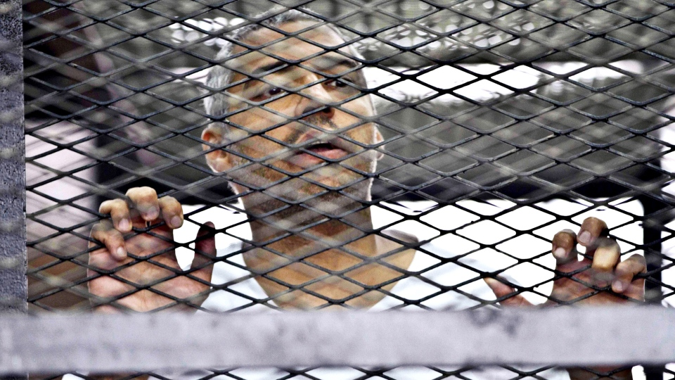 In this Thursday, May 5, 2014 photo, Mohammed Fahmy, Canadian-Egyptian acting bureau chief of Al-Jazeera, appears in a defendant's cage at a courtroom in Cairo, Egypt. (AP / Hamada Elrasam)