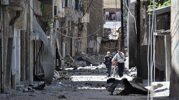 Syrians walk in destroyed alley damaged from Syrian army forces shelling, at Bab Sbaa neighborhood in Homs province, central Syria, Saturday, April 21, 2012. (AP)