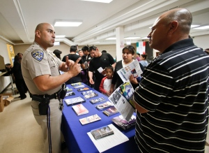 In this April 23, 2014, file photo, California Highway Patrol officer Armando Garcia explains to immigrants the process of getting a drivers license during an information session at the Mexican Consulate, in San Diego. California is gearing up to start issuing driver's licenses to immigrants in the country illegally in a bid to make the roads safer that could also give more than a million people access to state-issued identification. (AP Photo/Lenny Ignelzi,File)