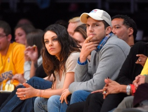 Actors Mila Kunis, left, and Ashton Kutcher watch the Los Angeles Lakers play the Oklahoma City Thunder in an NBA basketball game in Los Angeles, on Friday, Dec. 19, 2014. (AP / Mark J. Terrill)