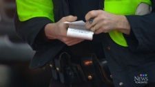 Officer handing out tickets in Toronto