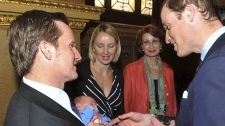 Prince William talks to Vic Vicary, who holds his three week old son Hugo Eric Scott Vicary, accompanied his wife Hanna, centre left, during a reception to celebrate the Scott-Amundsen Centenary Race to the South Pole at Goldsmiths Hall in the City of London, Thursday, April 26, 2012. (AP / John Stillwell)