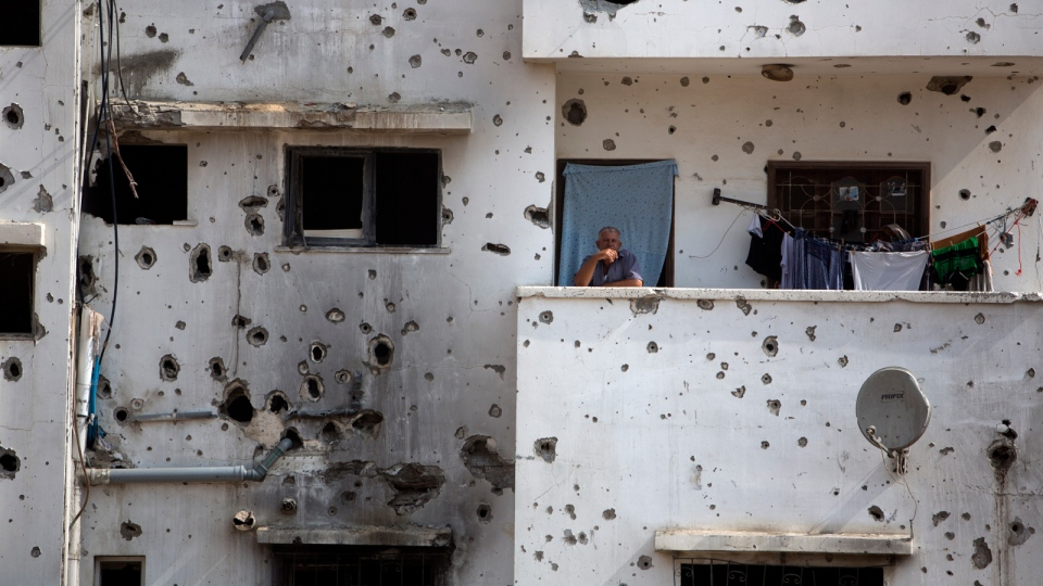 A Palestinian man stands on the balcony of his destroyed house as he waits for the visit of Palestinian Prime Minister Rami Hamdallah to Gaza's neighborhood of Shijaeyih, Thursday, Oct. 9, 2014. (AP / Khalil Hamra)