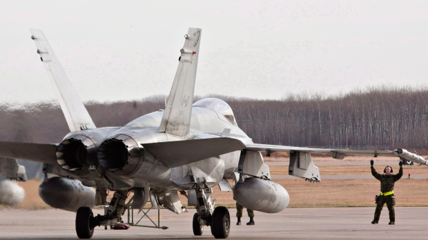 Military personnel guide a CF-18 Hornet into position at the CFB Cold Lake, in Cold Lake, Alta., on Tuesday, Oct. 21, 2014. (The Canadian Press/Jason Franson)
