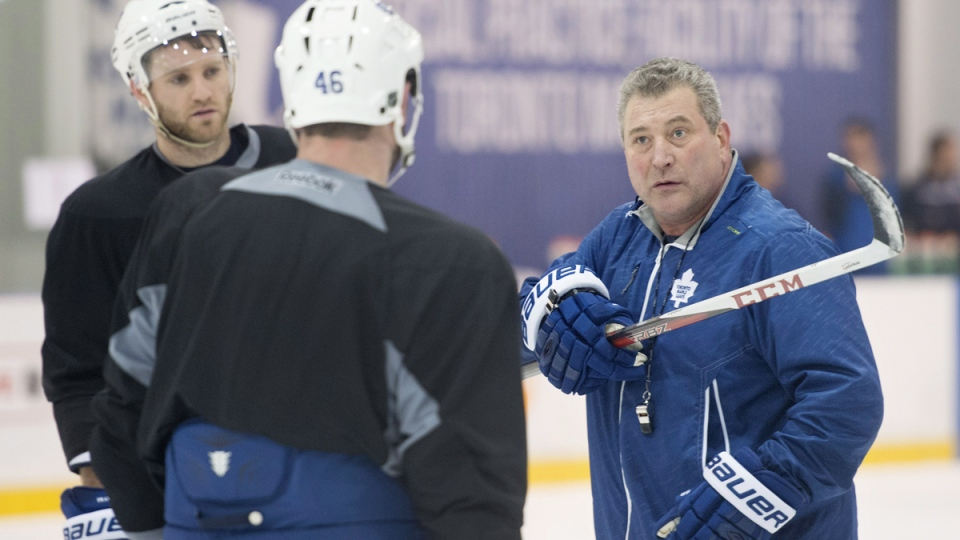 Peter Horachek, right, interim co-head coach of the Toronto Maple Leafs, explains a drill to Roman Polak (46) and Cody Franson during a practice at the team's practice facility in Toronto following the firing of head coach Randy Carlyle on Tuesday, Jan. 6, 2015. (Darren Calabrese / THE CANADIAN PRESS)