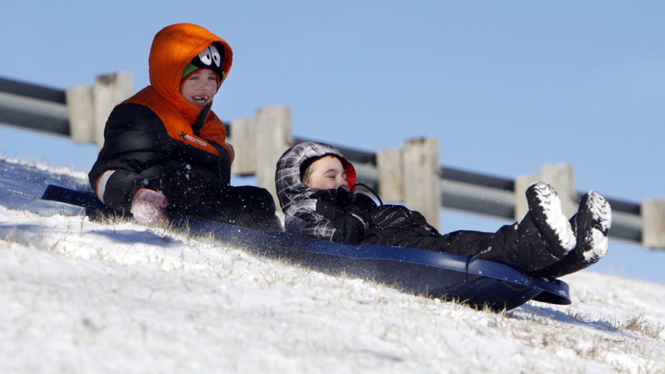 Magnus LeGron (left) and Quintin MacArthur, both 7, sled down the embankment at the K61 overpass at Avenue A, in Hutchinson, Kan., on Sunday, Jan. 4, 2015. (AP / The Hutchinson News, Lindsey Bauman)