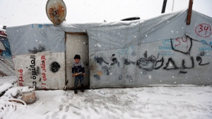 A Syrian boy stands at the door of his tent at a refugee camp in Deir Zannoun village, in the Bekaa valley, east Lebanon, Wednesday, Jan. 7, 2015. While the storm disrupted life for everyone, it proved particularly trying for the hundreds of thousands of Syrian refugees who live in tents and makeshift shelters in the Bekaa. The storm dumped rain and hail on Lebanon's coast and heavy snows in the mountains and central Bekaa Valley, where gas stations, banks, schools and most shops closed. (AP Photo/Hussein Malla)