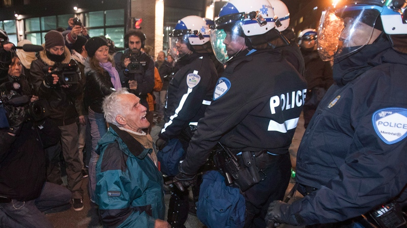 A man kneels in front of riot police as students protest against tuition fee hikes Friday, April 27, 2012 in Montreal. (Ryan Remiorz / THE CANADIAN PRESS)