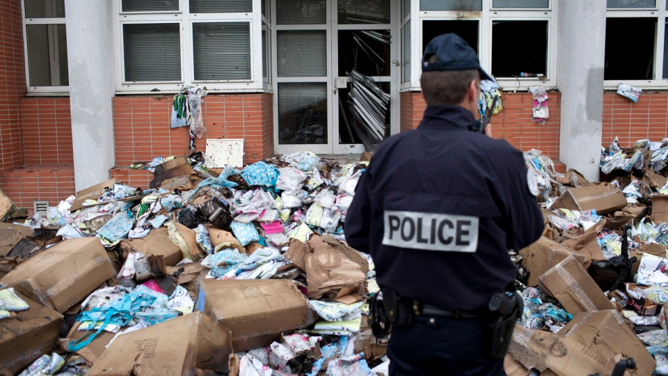 A police officer stands in front of the headquarters of satiric French newspaper Charlie Hebdo, that 'invited' the Prophet Muhammad as a guest editor in Paris, Wednesday, Nov. 2, 2011.  (AP / Thibault Camus)