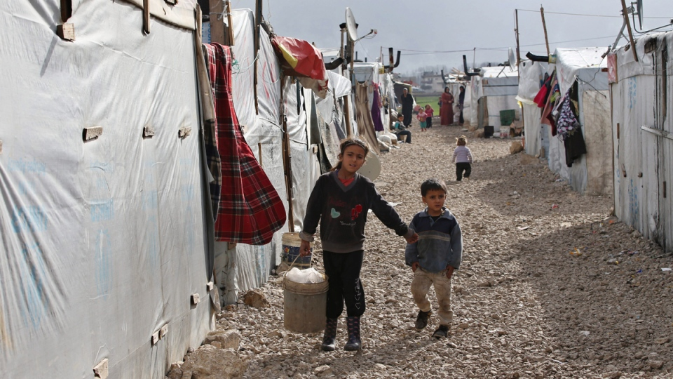 Syrian children walk between their tents at a refugee camp in Deir Zannoun village, Bekaa valley, Lebanon, on Jan. 6, 2015. (AP / Hussein Malla)