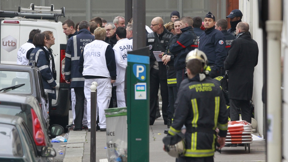 Police officers and rescue workers gather at the scene after gunmen stormed a French newspaper, in Paris, Wednesday, Jan. 7, 2015. (AP / Remy de la Mauviniere)