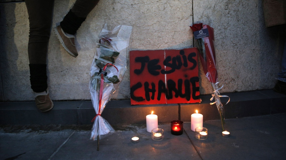 """Flowers, candles and a sign reading """"I am Charlie"""" are placed against a wall during a demonstration in Paris, Wednesday, Jan. 7, 2015. (AP / Christophe Ena)"""