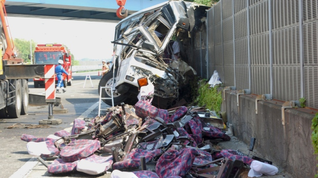 The wreckage of a destroyed bus is left on a highway in Fujioka, Gunma prefecture, north of Tokyo Sunday, April 29, 2012. (AP Photo/Kyodo News)
