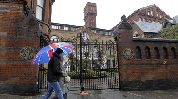 People walk past gated residential flats in Bow, east London, where the Ministry of Defence have warned residents that surface-to-air missiles could be stationed on their rooftops during the London Olympics, Sunday, April 29, 2012. (AP Photo/Sang Tan)