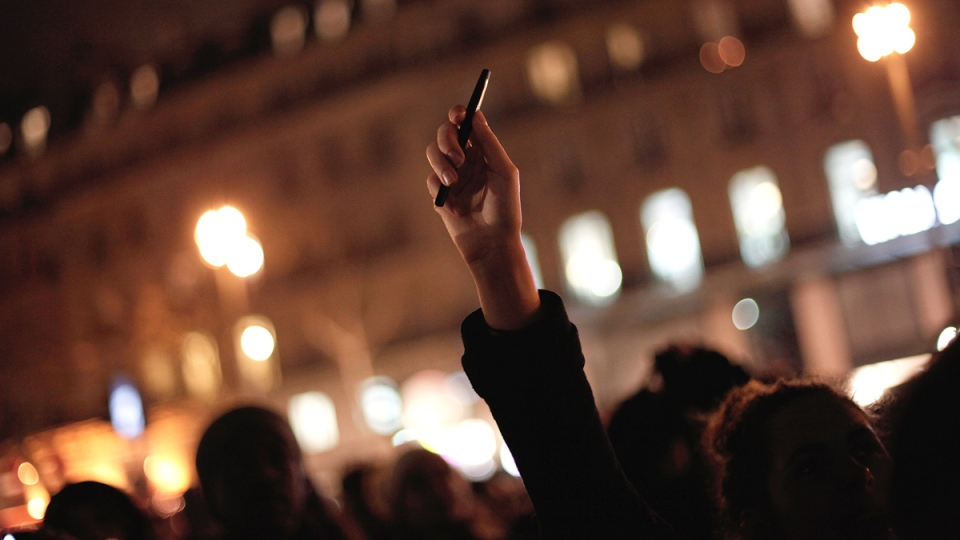 A woman holds up a pen during a gathering in solidarity of the victims of a terror attack against French satirical newspaper Charlie Hebdo in Paris, Wednesday, Jan. 7, 2015. (AP / Thibault Camus)