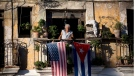 Javier Yanez stands on his balcony where he hung a U.S. and Cuban flag in Old Havana Cuba on Friday, Dec. 19, 2014. (AP / Ramon Espinosa)