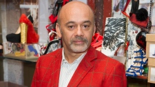 French shoe designer, Christian Louboutin, poses for photographers as he opens his first ever retrospective exhibition, at the Design Museum, London, Monday, April 30, 2012. (AP Photo/Jonathan Short)