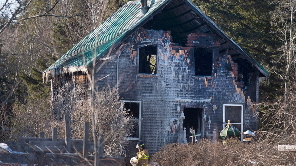 A firefighter works at the scene of a fatal house fire near Wyses Corner, N.S., outside of Halifax, on Thursday, Jan. 8, 2015. (Andrew Vaughan / THE CANADIAN PRESS)