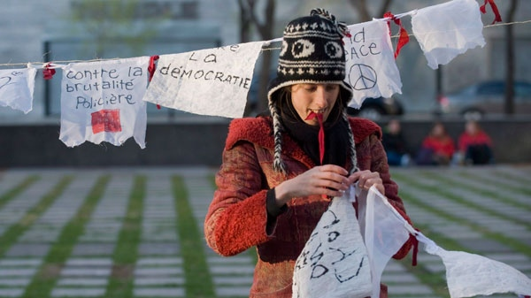 A protester opposing student tuition fee hikes hangs messages on a line during a demonstration in Montreal, Saturday, April 28, 2012. (Graham Hughes / THE CANADIAN PRESS)