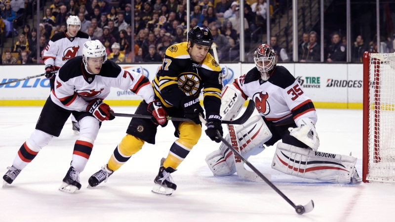 Boston Bruins left wing Milan Lucic skates between New Jersey Devils goalie Cory Schneider and defenseman Jon Merrill during the second period of an NHL hockey game in Boston, Thursday, Jan. 8, 2015. (AP/Charles Krupa)