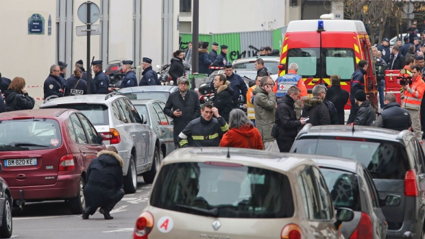 Police officers and rescue workers gather at the scene after gunmen stormed a French newspaper, killing at least 12 people, in Paris, France, Wednesday, Jan. 7, 2015. (AP / Remy de la Mauviniere)