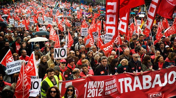 "People march with a banner that reads: ""Work, they want to finish with everything"" during the May Day rally in the center of Madrid, Tuesday, May 1, 2012. (AP / Daniel Ochoa de Olza)"
