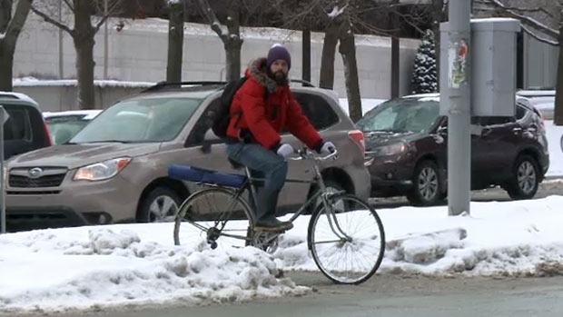 A cyclist negotiates snowbanks in Ottawa, Jan. 9, 2015