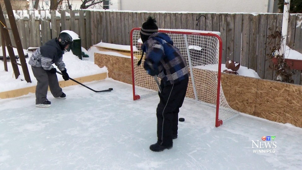 Connor Nairn and Connor Van Horne play hockey on a backyard outdoor rink in Winnipeg, Man., on Friday, Jan. 9, 2015.