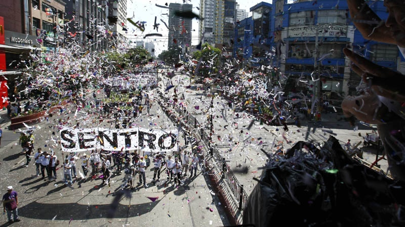 Supporters throw confetti at workers as they march for a rally near the Presidential Palace in Manila to celebrate international Labor Day known as May Day Tuesday May 1, 2012 in the Philippines.