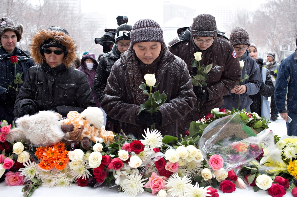 Mourners lay flowers during a public vigil for homicide victims in Edmonton, Alta., on Saturday, Jan. 10, 2015. (Jason Franson / THE CANADIAN PRESS)