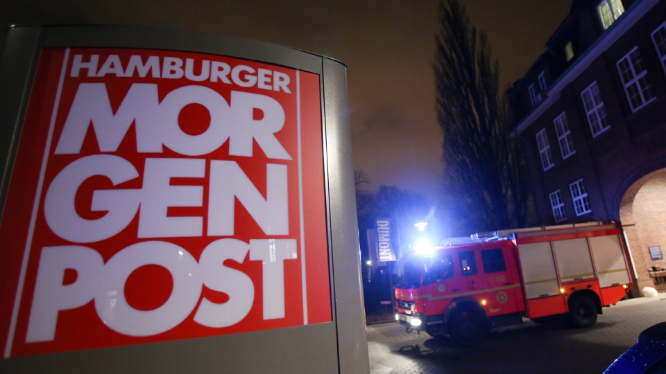 A fire truck sits outside the building of the 'Hamburger Morgenpost' in Hamburg, northern Germany, Sunday morning, Jan. 11, 2015. (AP / dpa, Bodo Marks)