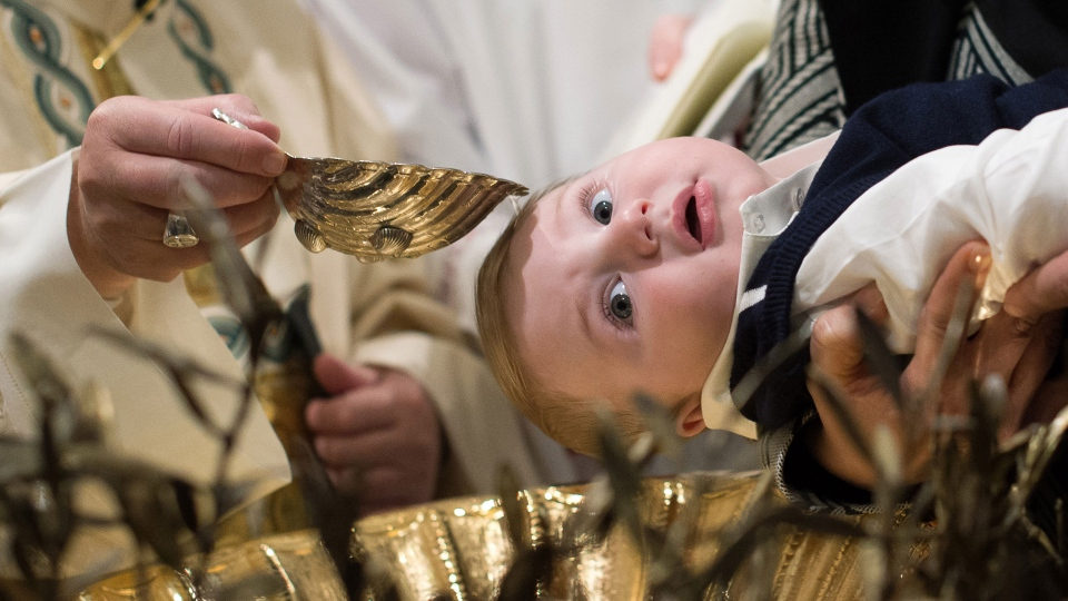 Pope Francis, left, baptizes a baby at the Vatican, Sunday, Jan. 11, 2015. (L'Osservatore Romano)