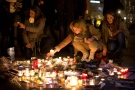 A woman lights a candle on Republique square during the demonstration in Paris, France, Sunday, Jan. 11, 2015. (AP / Peter Dejong)