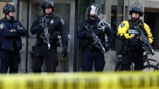 Police officers armed with riot gear stands guard outside the Jackson Federal Building during May Day protests in downtown Seattle, Washington, Tuesday, May 1, 2012. (AP / Ted S. Warren)