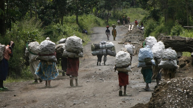 In this Nov. 19, 2008 women and traders travel from the charcoal market in Rupango, eastern Congo, through Kimoka. (AP Photo/Jerome Delay)