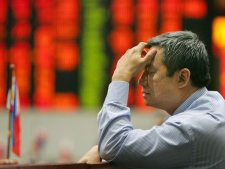 A trader contemplates as the electronic board shows figures in color red during trading at the Philippine Stock Exchange in Manila's financial district of Makati on Tuesday, Sept. 30, 2008. (AP / Pat Roque)