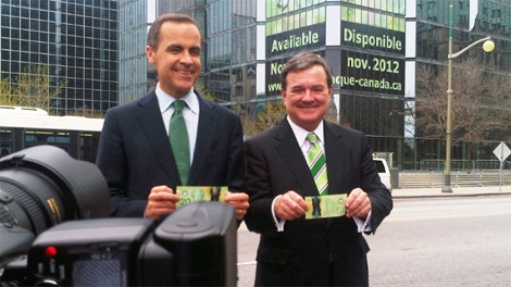 Bank of Canada Governor Mark Carney and Minister of Finance Jim Flaherty display the new $20 polymer banknote in Ottawa on Wednesday, May 2, 2012. (Richard Madan / CTV News)