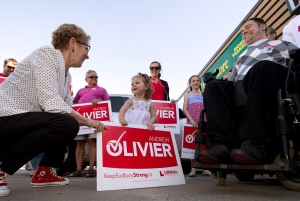 Ontario Liberal leader Kathleen Wynne greets two-year-old Ella Prosperi as she arrives at a campaign event for candidate Andrew Olivier (right) in Sudbury, Ontario on Tuesday May 27, 2014, 2014. (THE CANADIAN PRESS/Frank Gunn)