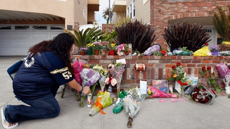 A San Diego Chargers fan wearing a Junior Seau NFL football jersey lights a candle at a makeshift memorial in front of Seau's house in Oceanside, Calif., Wednesday, May 2, 2012. (AP / Chris Carlson)