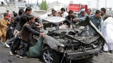 Afghans push a damaged car away from the scene of a militant attack in Kabul, Afghanistan, Wednesday, May 2, 2012. (AP / Ahmad Jamshid)