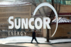 A pedestrian is reflected in a Suncor Energy sign in Calgary, Monday, Feb. 1, 2010. THE CANADIAN PRESS/Jeff McIntosh