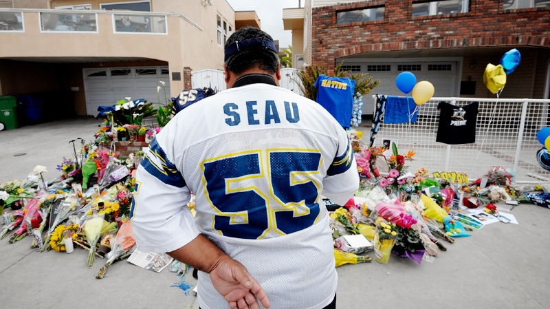 San Diego Chargers fan Jerry Lopez looks over a memorial set-up in the driveway of the house of former NFL star Junior Seau Thursday, May 3, 2012, in Oceanside, Calif. (AP / Denis Poroy)
