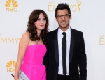 Zooey Deschanel, left and Jacob Pechenik arrive at the 66th Annual Primetime Emmy Awards at the Nokia Theatre L.A. Live in Los Angeles on Monday, Aug. 25, 2014. (Invision / Jordan Strauss)